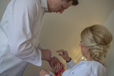 Bride helping her groom with his buttons on white shirt before going to wedding.