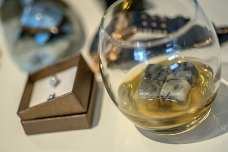 Pair of wedding rings in a box waiting beside a glass of whiskey. Stock Photo - 124062518