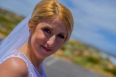 Happy just married bride in white dress smiling in beautiful sunny weather.