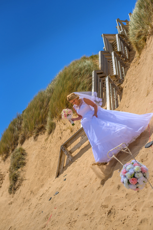 Bride in white wedding dress holding bouquet and posing at beautiful beach.
