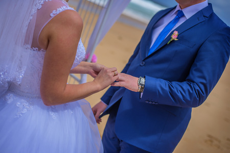 To be married couple exchanging rings while being married at beautiful beach. Stock Photo