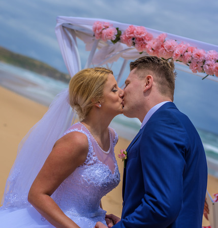 Couple kissing after just being married at beautiful Australian beach.