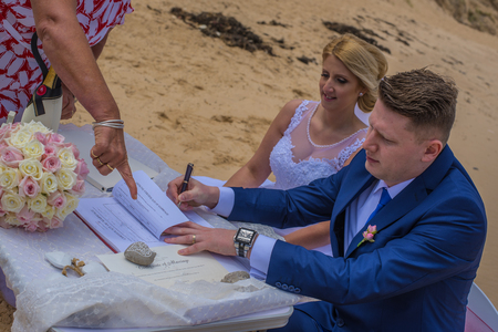 Just married couple signing marriage certificate at beautiful Australian beach.