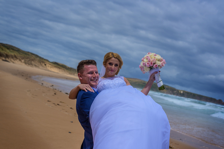 Man holding up his fresh wife in white wedding dress at beautiful beach.