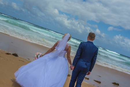 Just married couple holding bouquet at beautiful sandy beach by the sea. Stock Photo