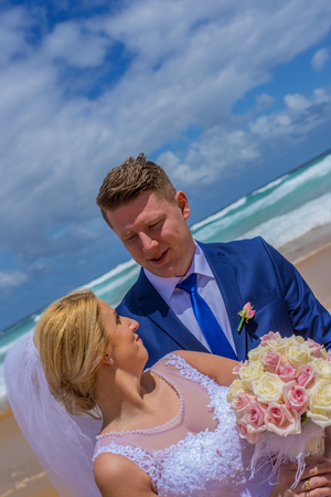 Just married couple standing on beautiful sandy beach with sea waves in back. Stock Photo