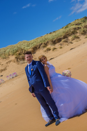 Just married couple standing on beautiful sandy beach on clear sunny day.