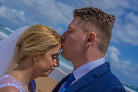 Just married man kissing his wife at forehead. Shot at sandy Australian beach. Stock Photo