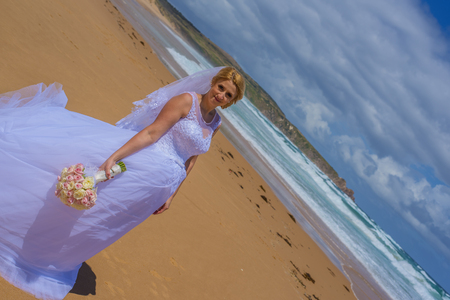 Bride in white wedding dress standing at beautiful sandy beach.