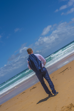 Man in blue suit standing at sandy beach watching the waves. Stock Photo