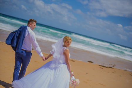 Freshly married pair holding hands while walking at beautiful beach in Australia Stock Photo
