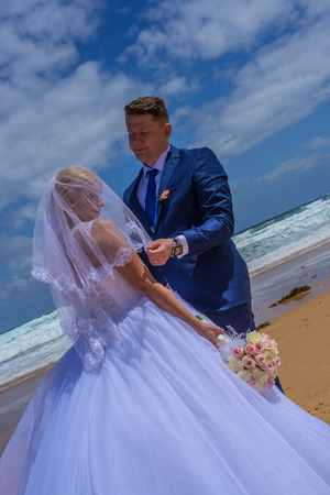 Just married couple holding bouquet at beautiful sandy beach and ocean. Stock Photo