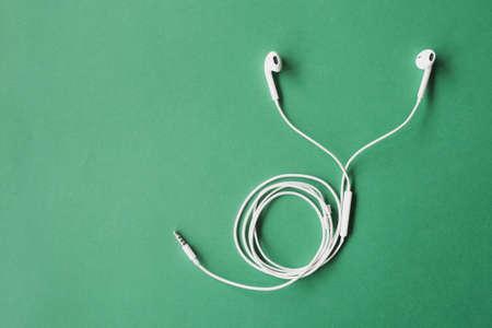 Earphone or earphones on  green background.the white earphones for using digital music or smart phone.