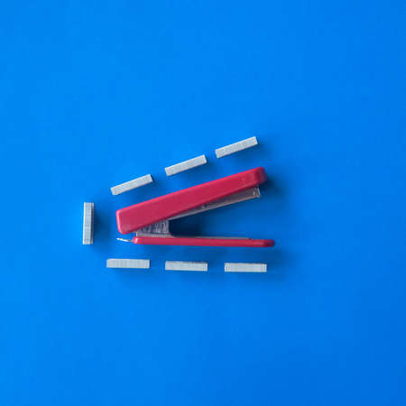 Red and white isolated metal stapler tool on blue background.creative idea.Flat lay. Stock Photo