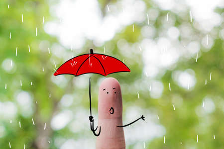 Finger art .Cute little boy holding an umbrella and dancing in rains on nature background for Monsoon Season.