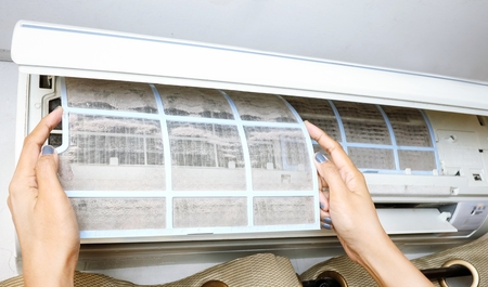 cleaning service: Removing dirty air conditioner filter for washing
