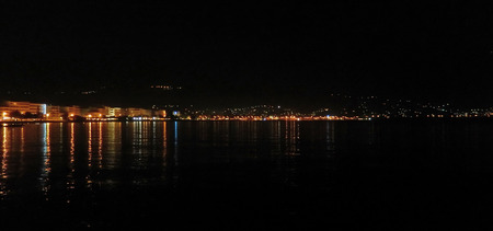 Harbor nightscape from the sea, with city lights reflecting in the Mediterranean in Kalamata, Greece Stock Photo