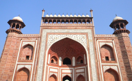 mogul: Decorated main gate portal to the Taj Mahal site in Agra, India, with floral marble inserts and Koran verses