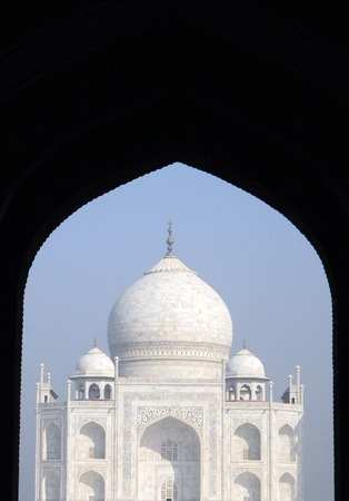 Iconic detail view of the Taj Mahal mausoleum in Agra, India, from an arched portal of the adjacent mosque