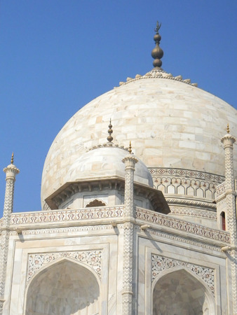 White marble details of the Taj Mahal mausoleum in Agra, India, with cupola and arches