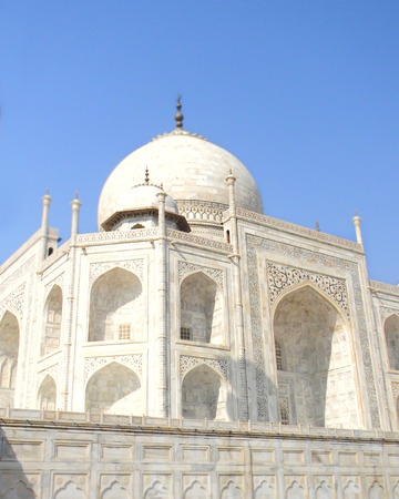 White marble details of the Taj Mahal mausoleum in Agra, India, with floral inserts and Koran verses