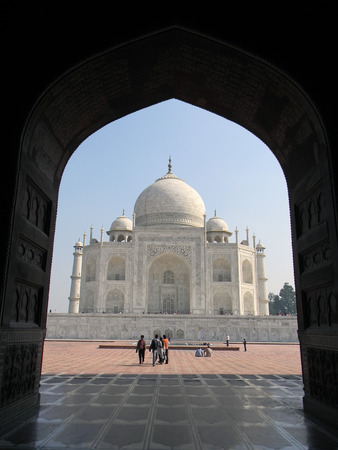 Iconic view of the Taj Mahal mausoleum in Agra, India, from an arched portal of the adjacent mosque
