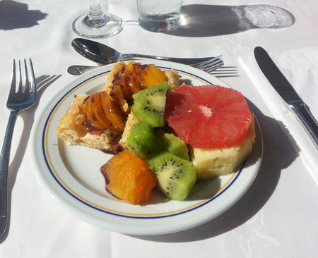 Breakfast plate with omelette, fresh kiwi, pineapple, mango and grapefruit slices, at an all-inclusive buffet