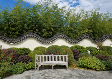 traditionally: Beautifully landscaped Chinese garden with traditionally decorative walls and bench