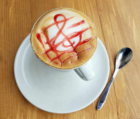 g clef: Delicious cappuccino cup with froth and musical G clef sign out of sugary cream