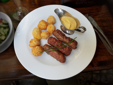 Traditional Romanian meat rolls with cheese balls and mustard