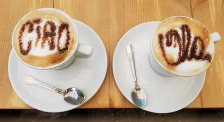 Delicious cappuccino coffee cups with creamy froth design with greetings