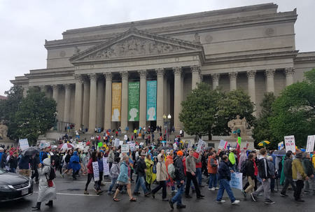 WASHINGTON, DC - JANUARY 21, 2017 Protesters hold signs signalling their support for science and scientific research in front of the National Archives, home of the Constitution of the United States, as thousands participate in the March for Science, a glo