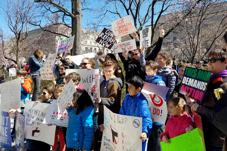 WASHINGTON, DC, USA - MARCH 24, 2018: People hold signs in the March For Our Lives, a student-led rally, demanding an end to gun violence and responsible firearm control legislation.