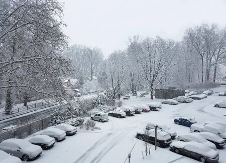 Aerial view of a parking lot with Cars covered in snow during a snowstorm for winter backgrounds