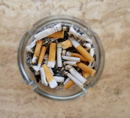 Ashtray with numerous cigarette butts for smoking addiction backgrounds. Foto de archivo