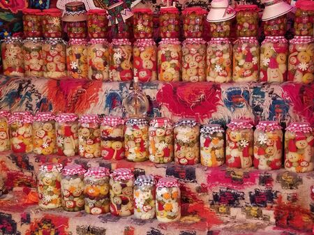 Pickle jars decorated with happy faces, on a Christmas fare display in the city of Timisoara, Romania.