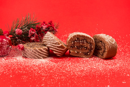 swiss roll: Christmas chocolate Swiss roll cake isolated on red background