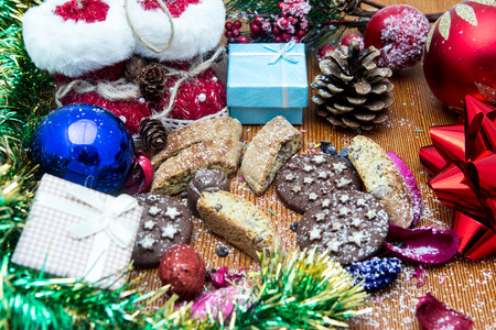 pine wreaths: Christmas still life with ginger honey biscuits, ornaments, pine, shoes, gift, wreaths chocolate candy on a wooden background
