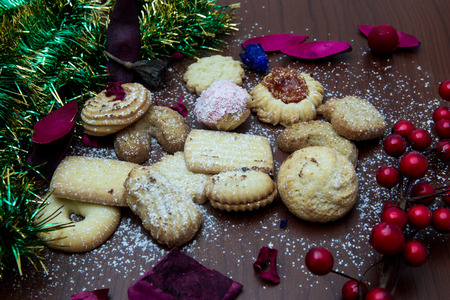 Christmas still life with ginger honey biscuits, ornaments, pine, shoes, gift, wreaths chocolate candy on a wooden background