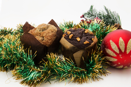 Christmas still life with ginger honey muffins, ornaments, pine, shoes, gift, wreaths chocolate candy on a wooden background