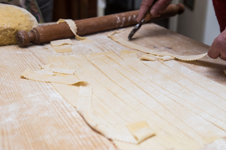 crostoli: Woman hands kneading dough on kitchen table with rolling pin