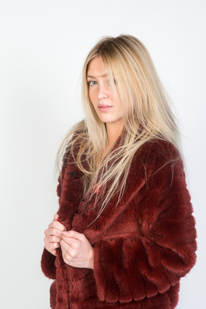 furs: Portrait of a beautiful model with provocative glam makeup wearing red fur,. Natural furs concept. Studio shot.