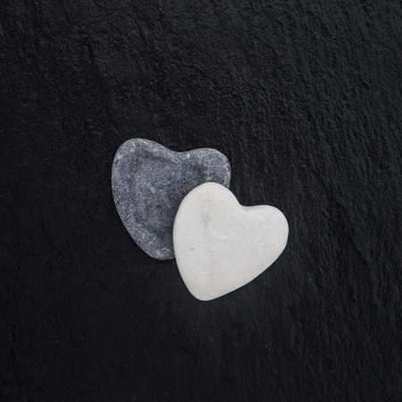 st valentin: Heart-shaped sea stone on black background Stock Photo