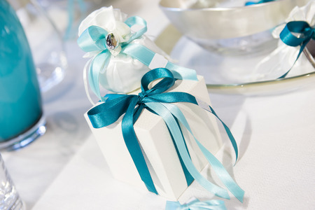 white gift box with blue bow ribbon