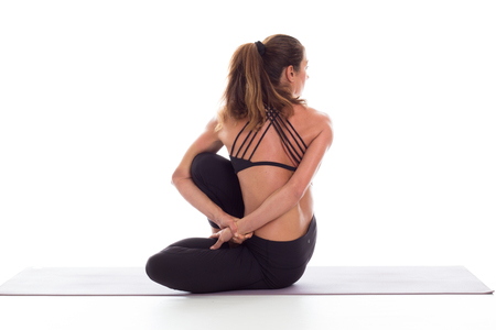 Studio shot of a young fit woman doing yoga exercises white background,