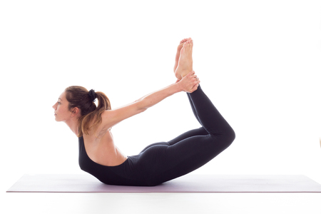 Studio shot of a young fit woman doing yoga exercises white background