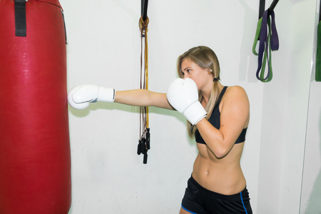 sexy fighter girl punching actively. motion long hair, and wearing a boxing gloves