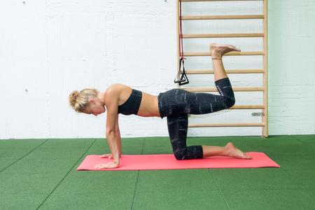 Fitness girl stretching legs doing pilates legs stretches exercises in gym. athlete exercising abductor hip flexor muscle.