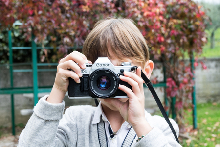 Trieste, Italy - October 22nd 2017: Camera Canon AE-1 35mm, baby taking pictures using vintage movie camera