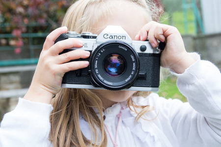Trieste, Italy - October 22nd 2017: Camera Canon AE-1 35mm, little girl taking photos using vintage movie camera